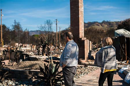 photo of a man and a woman staring looking at their destroyed home